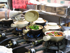 An array of clay pots cooking on a modern range